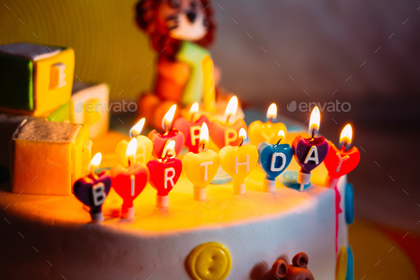 Happy Birthday Written In Lit Candles On Colorful Cake - Stock Photo - Images