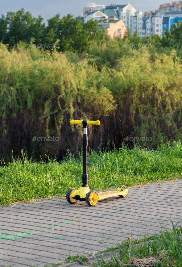Three wheel adjustable height yellow scooter - Stock Photo - Images