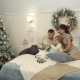Family Is Lying on the Bed Near the Christmas Tree - VideoHive Item for Sale