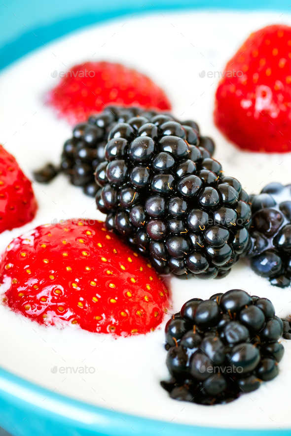 Blackberries and strawberries in yogurt. - Stock Photo - Images
