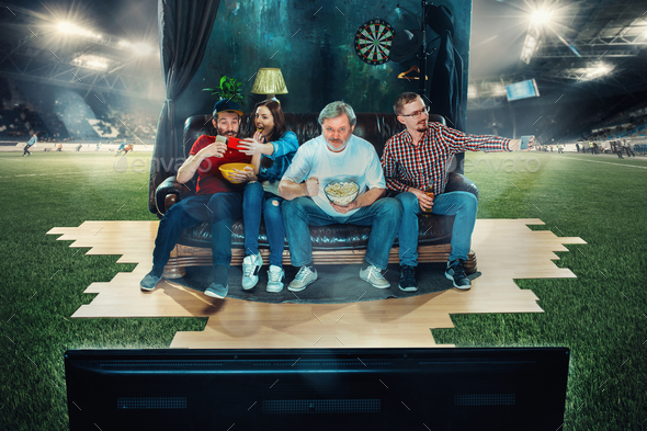 Soccer football fans sitting on the sofa and watching TV in the middle of a football field. - Stock Photo - Images