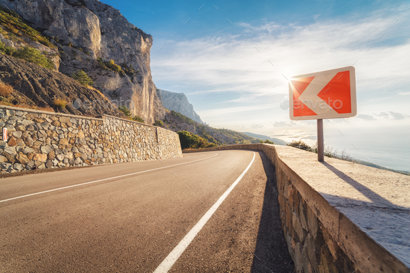 Asphalt road and road sign in mountains at sunset - Stock Photo - Images