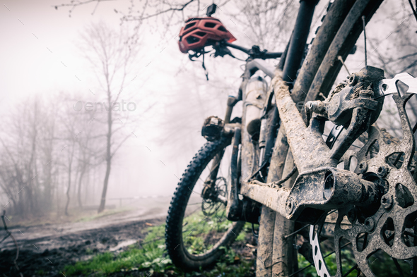 Mountain bike and helmet in autumn woods, dirty bicycle - Stock Photo - Images