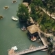 Exotic Bungalows with Thatched Roof and Boat Pier on Shore Green Lake Aerial View. Drone View - VideoHive Item for Sale