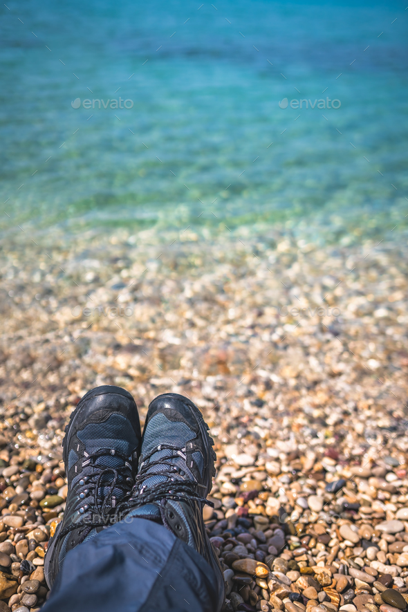 Trekker feet on the stony beach - Stock Photo - Images
