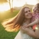 Happy Mother Hugs Adorable Little Daughter and Whirls with Her in Sunny Park - VideoHive Item for Sale