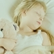Little Girl Is Sleeping in Bed. Cuddles a Toy Bear - VideoHive Item for Sale