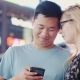 A Young Multi-ethnic Couple Uses a Smartphone. Night City Against a Background of Blurry Lights - VideoHive Item for Sale