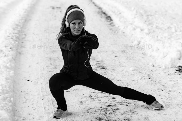 Female athlete exercising in park in winter - Stock Photo - Images