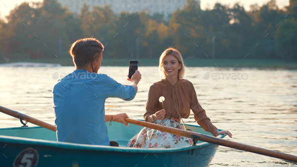 Smiling young couple in a boat - Stock Photo - Images