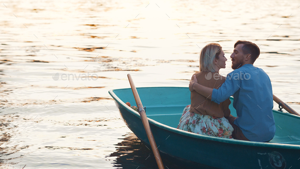 Embracing young coupl? in a boat - Stock Photo - Images