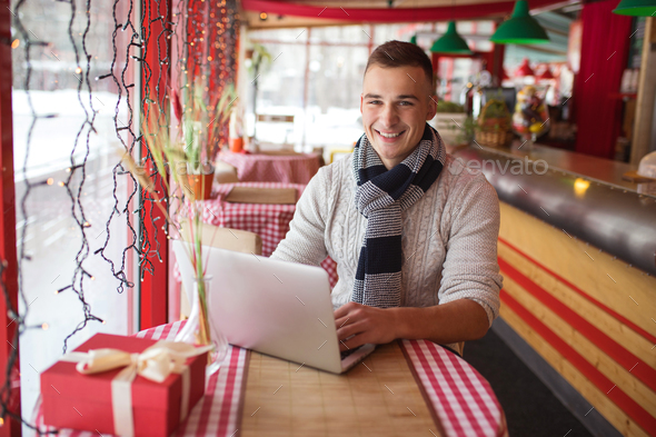 Smiling young man with laptop - Stock Photo - Images