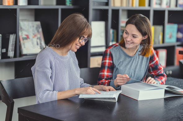 Smiling girls with laptop in a bookstore - Stock Photo - Images