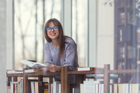 Smiling student in the library - Stock Photo - Images