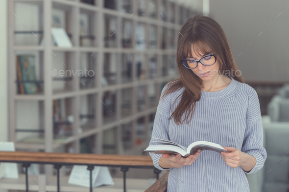 Young girl reading a book in the library - Stock Photo - Images