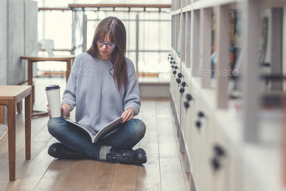 Young woman reading a book indoors - Stock Photo - Images