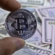 Hand in Fingers Holds a Silver Coin Bitcoin, BTC on a Background with Bills of Dollars - VideoHive Item for Sale