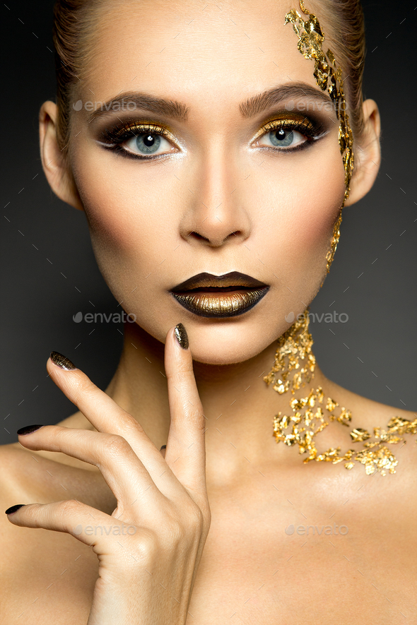 Beautyful girl with gold glitter on her face and body - Stock Photo - Images