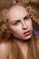 Beautiful blonde model girl with long curly hair .