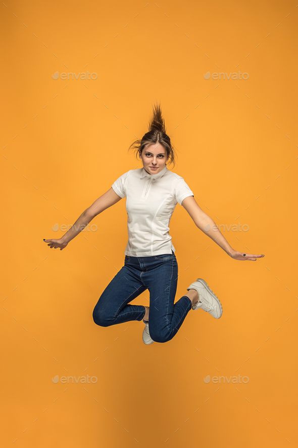 Freedom in moving. Pretty young woman jumping against orange background - Stock Photo - Images