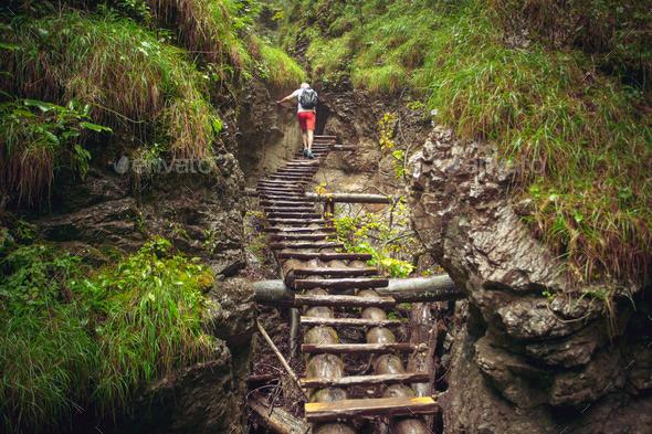 Hiker walking hard way through the canyon - Stock Photo - Images