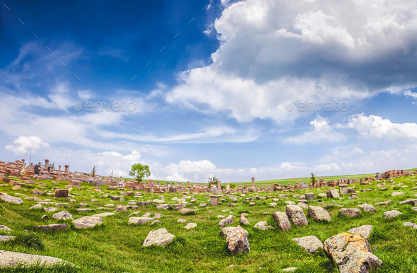 Stones on lawn and magnificent cloudy sky - Stock Photo - Images