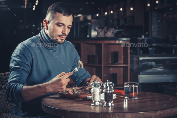 man eating in a restaurant - Stock Photo - Images