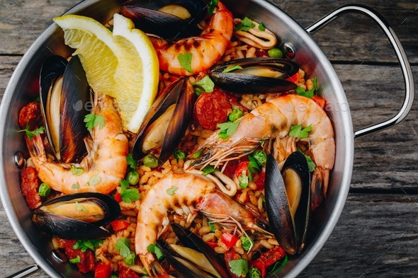 Spanish seafood paella with mussels, shrimps and chorizo sausages in traditional pan - Stock Photo - Images
