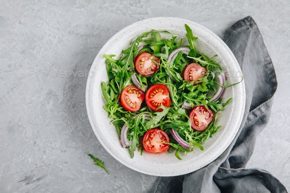 Green salad arugula with tomatoes and red onion in bowl - Stock Photo - Images