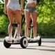 Two Beautiful Young Girls in Sexy Clothes Are Laughing and Dancing While Riding on Segway in the - VideoHive Item for Sale