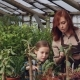 Adorable Girl Is Helping Her Mother in Greenhouse Counting Pot Plants While Her Mom Is Working - VideoHive Item for Sale