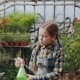 Daughter of Greenhouse Owner Is Helping Her Mother in Workplace Sprinkling Water on Seedlings - VideoHive Item for Sale