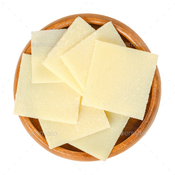 Parmesan cheese slices in wooden bowl over white - Stock Photo - Images
