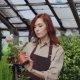 Young Woman Gardener Wearing Apron Is Watering Pot Plant and Checking Leaves While Working Inside - VideoHive Item for Sale