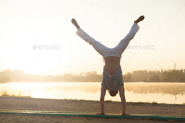 Athletic capoeira performer workout training on the beach sunris - Stock Photo - Images