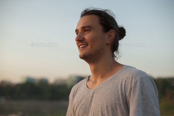 Handsome man smiling in the park - Stock Photo - Images