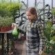 Adorable Girl in Apron Is Watering Flowers with Spray Bottle While Her Pretty Mother Is Working - VideoHive Item for Sale