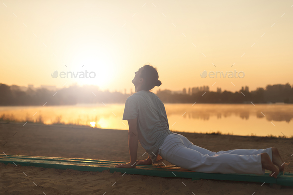 Young athletic men doing yoga on the sand in the park - Stock Photo - Images