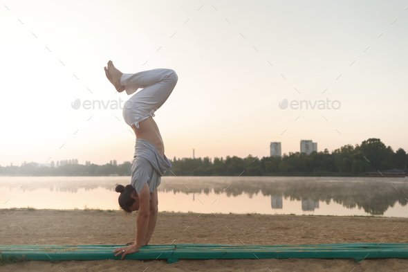 Young athletic man doing yoga poses near the lacke - Stock Photo - Images