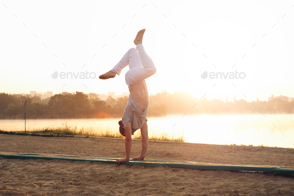 Athletic young man workout mornings in the park near lake - Stock Photo - Images