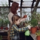 Curious Little Girl Is Helping Her Mom To Spray Plants with Water From Spraybottle While Working - VideoHive Item for Sale
