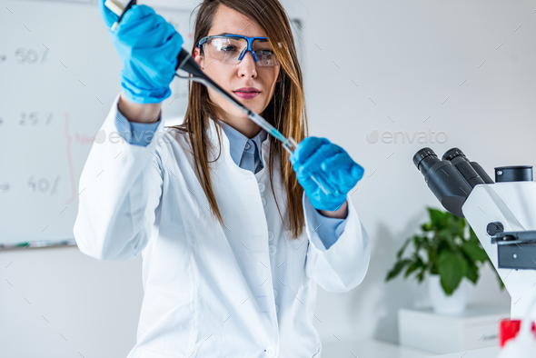 Laboratory technician with micro pipette - Stock Photo - Images