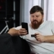 Serious Fat Man Types a Number of His Credit Card in the Smartphone Sitting on the Couch - VideoHive Item for Sale