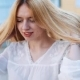 Wind Blows Woman's Blonde Hair While She Stands Outside - VideoHive Item for Sale