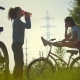 Two Cyclists, One Girl Warms Up, the Other Drinks Water and Resting Before Cycling - VideoHive Item for Sale