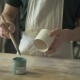 At the Desk Artist Paints a Clay Mug with a Blue Brush - VideoHive Item for Sale