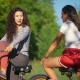 Two Young Cyclists Communicate and Laugh on a Cycling Trip in the Park, on a Sunny Summer Day - VideoHive Item for Sale