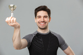 Happy young sportsman holding award. - PhotoDune Item for Sale