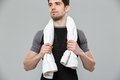 Handsome young sportsman holding towel looking aside.