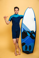 Happy young man dressed in swimsuit pointing. - PhotoDune Item for Sale